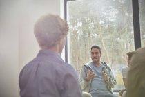 Homem falando e gesticulando numa sessão de terapia de grupo — Fotografia de Stock