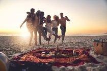 Игривые юные друзья пинаются, наслаждаясь пикником на солнечном летнем пляже — стоковое фото