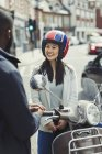 Smiling young woman in helmet on motor scooter, talking to friend on urban street — Stock Photo