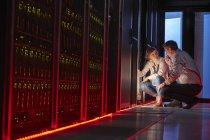 Це техніків говорити на панелі світиться в кімнаті темно сервера — стокове фото