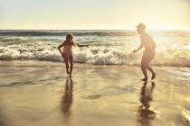 Verspielte junge Paar im nassen Sand laufen auf sonnigen Sommer Meer Strand — Stockfoto