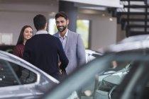 Vendeur de voitures d'accueil, se serrant la main avec des clients de couple dans le showroom du concessionnaire voiture — Photo de stock