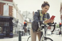 Young woman texting with cell phone, commuting on bicycle on urban street — Stock Photo