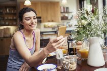 Smiling young woman texting with smart phone at breakfast table — Stock Photo