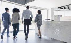 Uomini d'affari che camminano nella hall dell'ufficio — Foto stock
