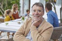 Portrait homme âgé souriant profitant d'un déjeuner patio en famille — Photo de stock