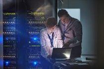 Он техников, работающих на ноутбук в темных серверной комнаты — стоковое фото