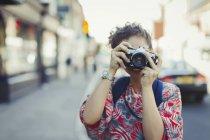 Ritratto giovane donna che fotografa con macchina fotografica sulla strada — Foto stock