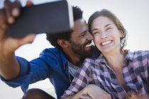 Smiling, enthusiastic multi-ethnic couple taking selfie with camera phone — Stockfoto