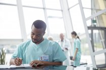 Male nurse reviewing medical record in hospital lobby — Stock Photo