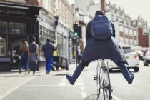 Playful young businessman commuting, riding bicycle on sunny urban street — Stock Photo