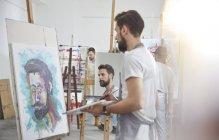 Чоловічий художників, живопис на мольберті у мистецтві клас студії — стокове фото