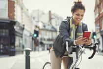 Smiling young woman commuting with bicycle, texting with cell phone on sunny urban street — Stock Photo
