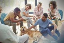 People petting dog in group therapy session — Stock Photo
