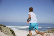 Pre-adolescent boy running on sunny summer ocean beach — Stock Photo