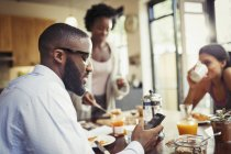 Man drinking coffee and texting with smart phone at breakfast table — Stock Photo