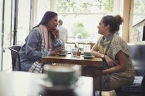 Women friends drinking coffee and talking at cafe table — Stock Photo