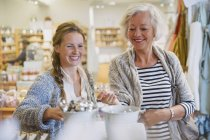 Smiling mother and daughter browsing merchandise in shop — Stock Photo