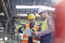 Мужчина бригадир и рабочий с планшетом разговаривают на заводе — стоковое фото