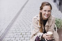 Portrait smiling woman drinking iced coffee at sidewalk cafe — Stock Photo