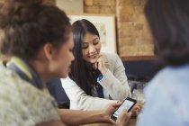Junge Freundinnen mit Smartphone im Café — Stockfoto