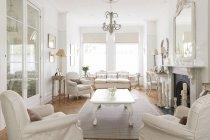 Blanc luxe maison vitrine intérieur salle de séjour avec cheminée et lustre — Photo de stock