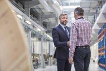 Proprietário do negócio e supervisor handshaking na fábrica de fibra óptica — Fotografia de Stock