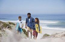 Familia caminando con tablas en la playa de mar soleado de verano - foto de stock