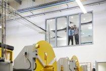 Начальники мужского пола разговаривают у окна над заводским этажом — стоковое фото