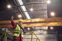 Métallos parler, à l'aide de talkie-walkie sur plate-forme en aciérie — Photo de stock