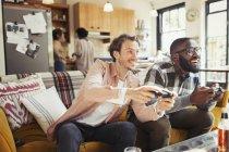Amis hommes, jouant le jeu vidéo dans le salon — Photo de stock