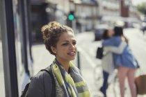 Nachdenkliche junge Frau Wegsehen auf sonnigen urban street — Stockfoto