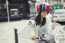 Smiling young woman texting with cell phone on motor scooter, wearing helmet on urban street — Stock Photo