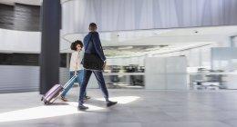 Homme d'affaires et femme d'affaires à pied, tirant la valise dans le hall de bureau moderne — Photo de stock