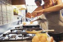 Junge Frau knacken Ei in Pfanne auf Herd in der Küche — Stockfoto