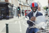 Усміхаючись Молодий підприємець у шолом на моторолер текстові повідомлення з мобільного телефону на міських вулиць — стокове фото