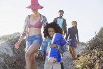 Sorrindo família andando na ensolarada colina de praia de verão — Fotografia de Stock