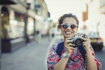Портрет улыбающейся юной туристки в солнечных очках, фотографирующей с камерой на городской улице — стоковое фото