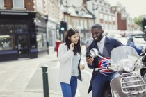 Young couple using cell phone at motor scooter on sunny urban street — Stock Photo