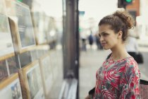 Young woman browsing real estate listings at urban storefront — Stock Photo