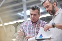 Male supervisors with clipboard examining fiber optic cable in factory — Stock Photo