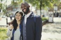 Усміхаючись, ласкава молода пара обіймає в Сонячний міський парк — стокове фото