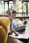 Female freelancer working at laptop, taking notes on living room floor — Stock Photo