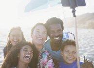 Prise familiale multiethnique heureux, enjoué selfie avec selfie bâton sur la plage ensoleillée de l'été — Photo de stock