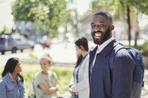 Portrait homme d'affaires souriant avec sac à dos dans un parc urbain — Photo de stock
