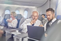Businessmen working at laptop in first class on airplane — Stock Photo