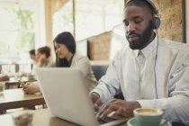 Hombre joven con auriculares usando el ordenador portátil y beber café en la mesa de café - foto de stock