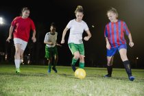 Young female soccer players playing soccer on field at night, kicking the ball — Stock Photo