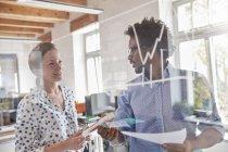 Pessoas de negócios com gráfico revisão de papelada em vidro no escritório — Fotografia de Stock