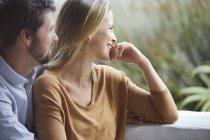 Улыбающаяся пара смотрит в сторону патио — стоковое фото
